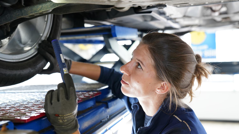 Eine TÜV SÜD Prüfingenieurin untersucht ei Fahrzeug im Rahme der Hauptuntersuchung